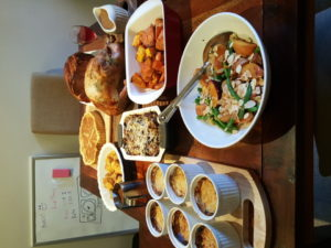 A table set with many dishes of food including a quiche, ham, turkey and several sides.