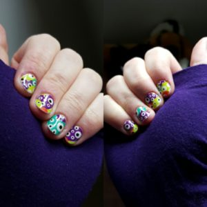 Two hands showing nails over dark purple sleeves, fair Caucasian skin tone with nail wraps featuring glow in the dark multi-coloured eyeballs from Jamberry.