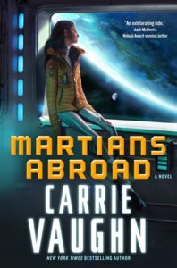 A woman sits by a spaceship window with the glow of the Earth in silhouette visible. The title Martians Abroad is in orange, the author Carrie Vaughn's name is in white both in large letters at the bottom of the image.