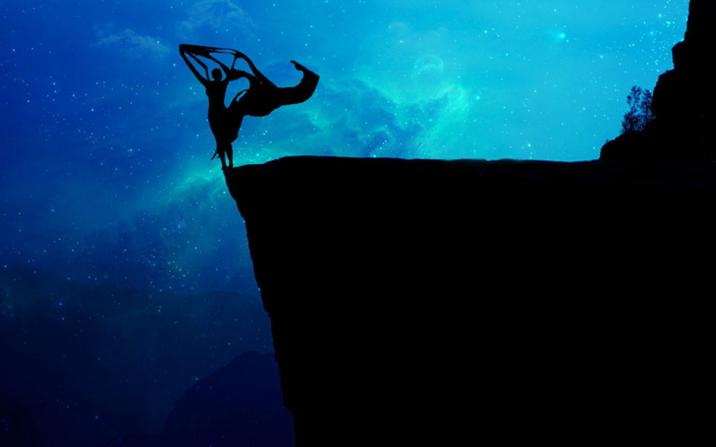 Silhouette of a cliff with a blue starscape behind it. Standing on the edge of the cliff is a female figure with scarves uplifted by a breeze.