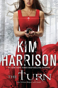 Book cover with a grey forest background with a long haired brunette woman in a flowing red dress holding a rotting piece of fruit in her cupped hands that spills black down the front of the dress.