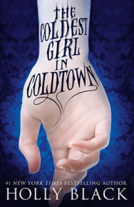 A pale skinned hand is shown palm forward, fingers slightly curled with a background of deep dark blue. The title 'The Coldest Girl in Coldtown' is shown on the wrist like a cursive tattoo.