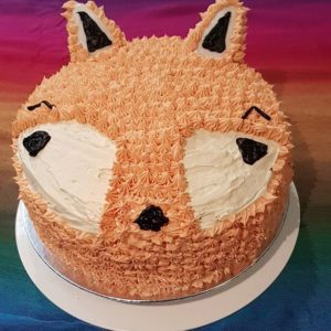 A fluffy looking cake of a Fox face with icing ears stuck on and orange icing, black detailing and white cut outs. Background is rainbow fabric.